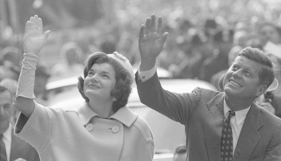 Jackie y John F Kennedy saludan a la multitud