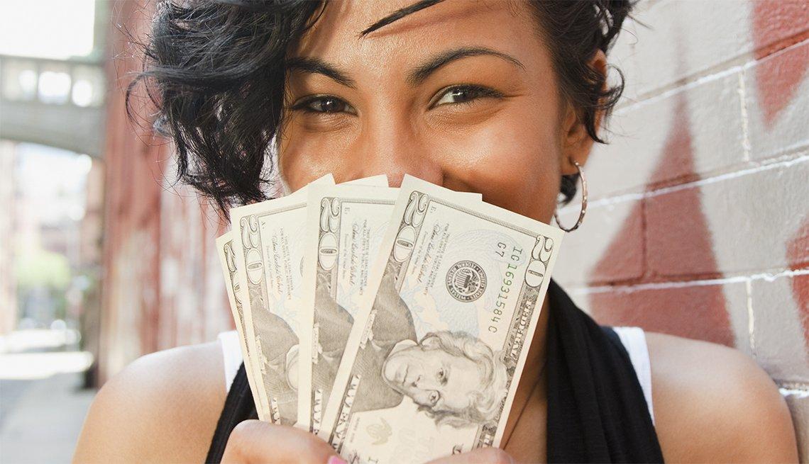 Joven hispana sonriendo y mostrando varios billetes de dolar que sostiene frente a su cara