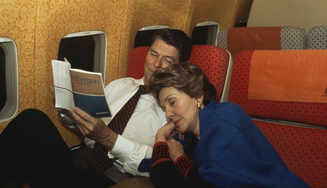 Ronald y Nancy Reagan aborodo de un avión, ella durmiendo y él leyendo un libro