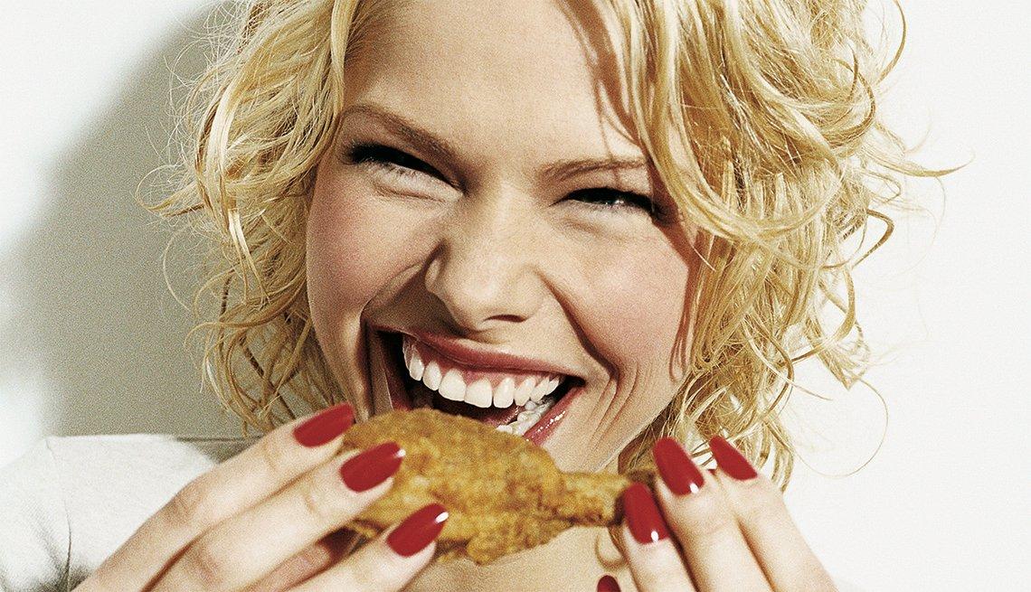 Mujer sonriendo y a punto de comer una pierna de pollo