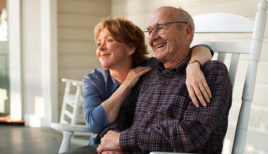Mature woman's arms around mature man, laughing, on porch, Public Policy Institute, Initiatives, Caregivers