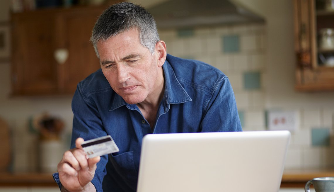 Man, looking at credit card, computer, inside a house, Public Policy Institute, Consumer Protection