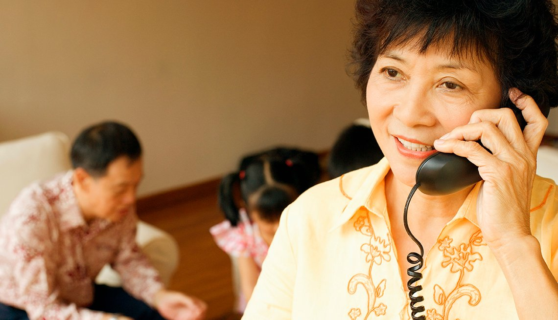 Mature Asian woman, using landline telephone, Telecommunications,  AARP Research, Technology