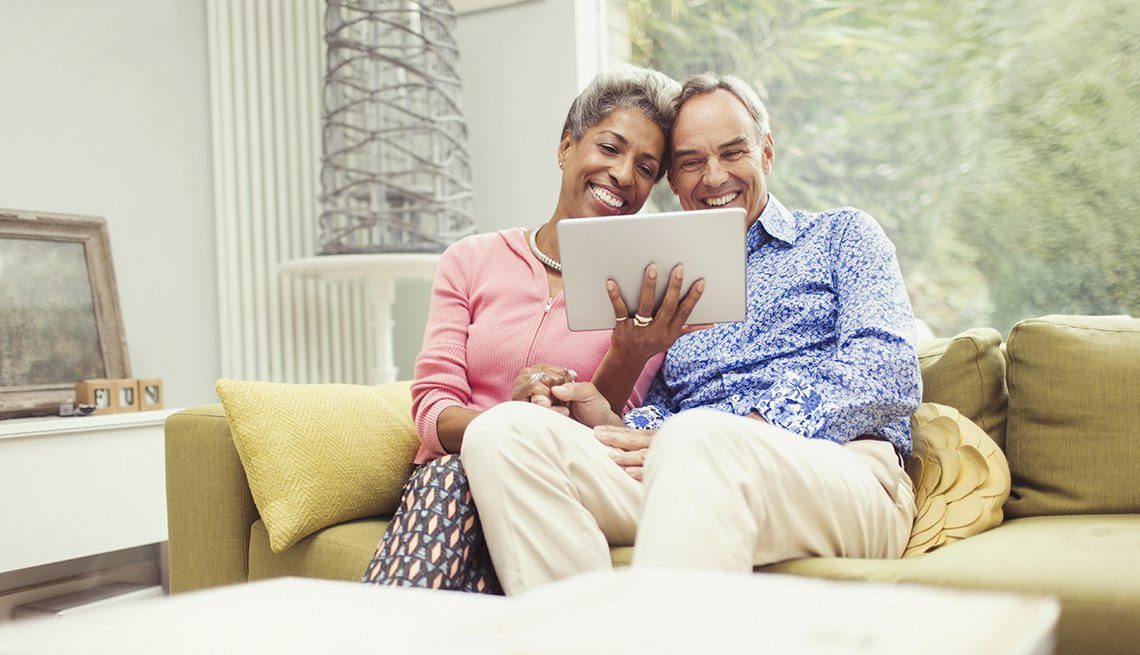 couple sitting on couch looking at a tablet