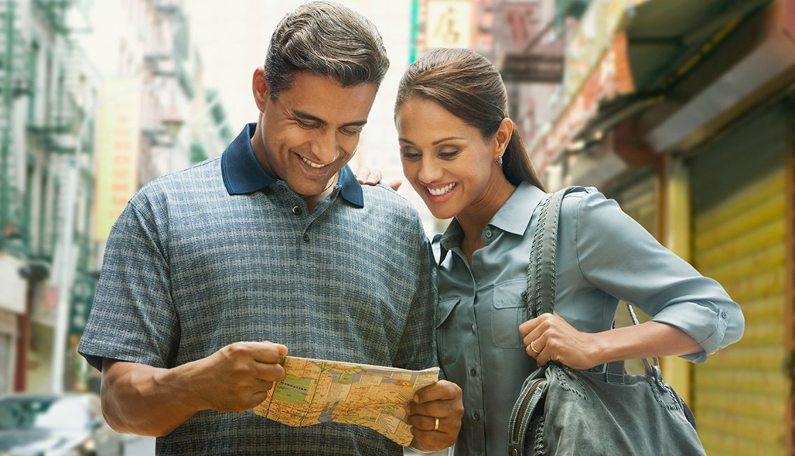 couple standing in the street smiling and looking at a map