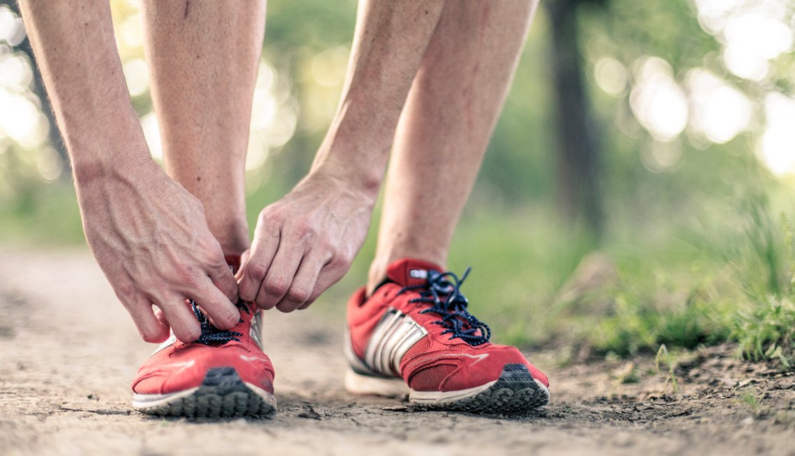 hands of a man tying a knot in the laces of his running shoe