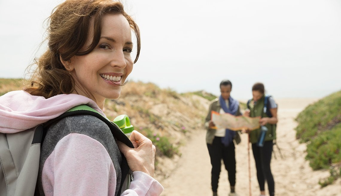 woman smiling with a backpack hiking with friends