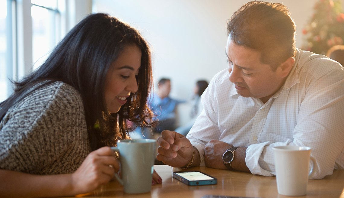 Hispanic Husband and Wife Using Cell Phone, Earn Rewards, AARP Rewards for Good