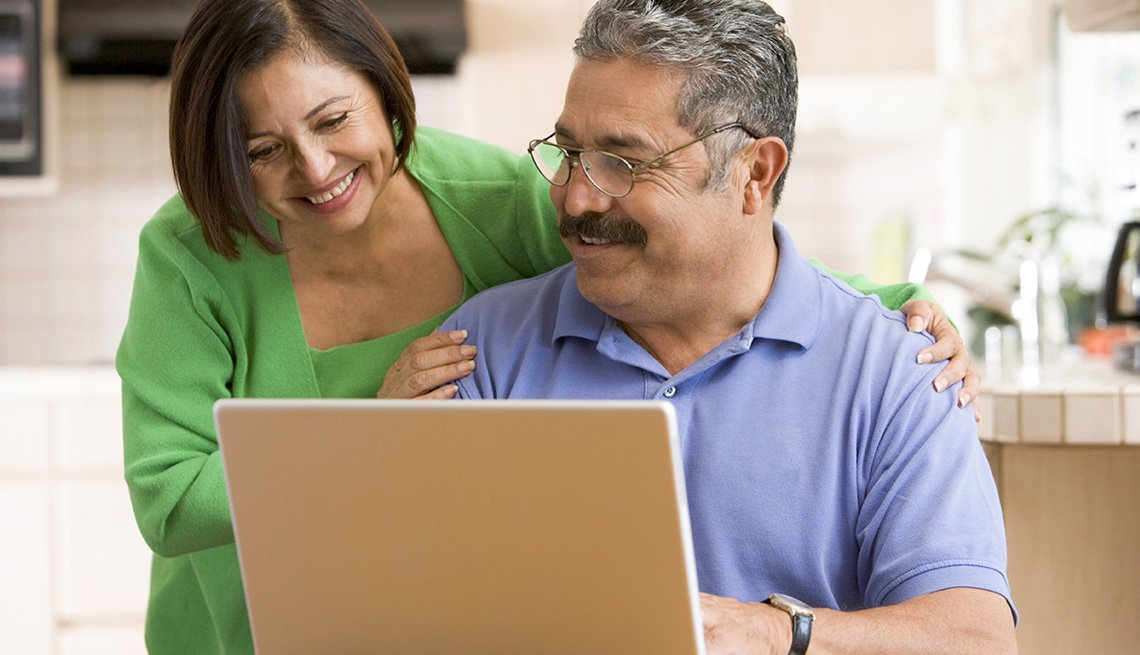 Technology, Mature man and woman smiling at laptop in kitchen setting