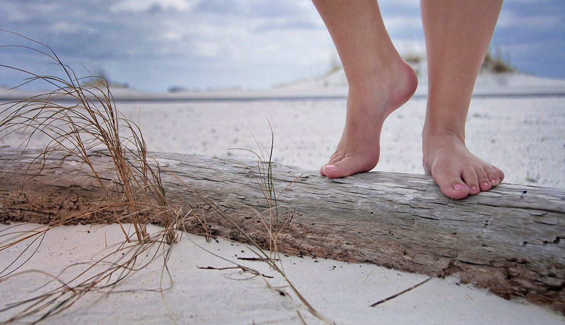 Close Up Of A Woman's Feet And Legs On Driftwood On Beach In Pensacola Florida, Top USA Destination Cities