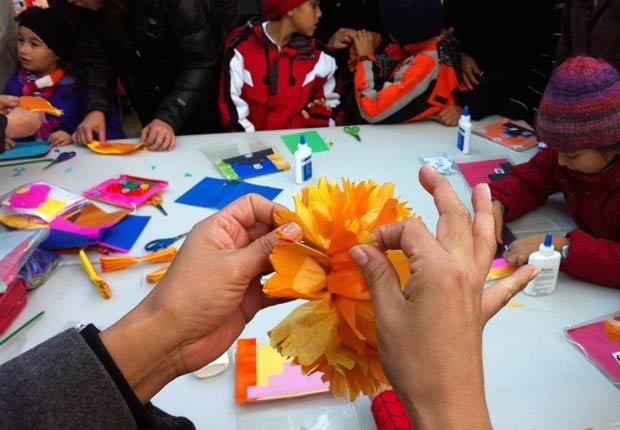 Niños hacen objetos en papel en un taller en el Día de los Muertos