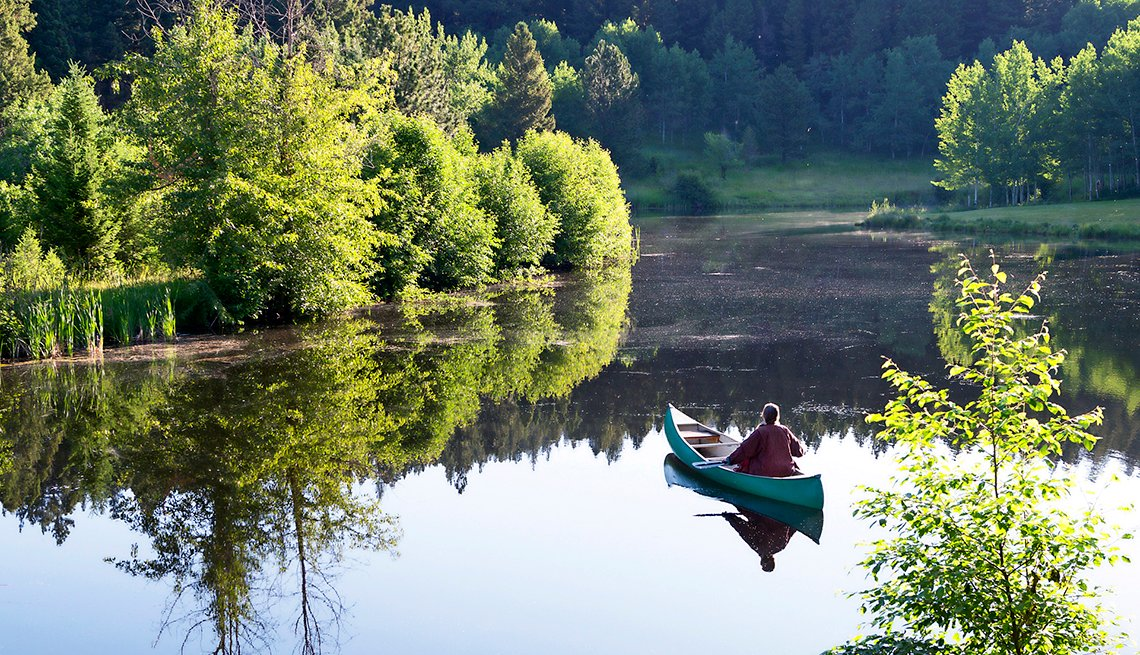 Man in Canoe on Lake at Feathered Pipe Ranch in Montana, Yoga Retreat Vacations