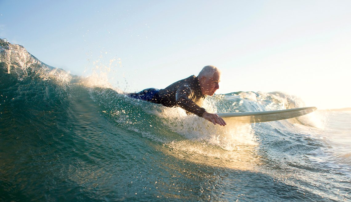 Older man in wetsuit surfing a wave at sunset