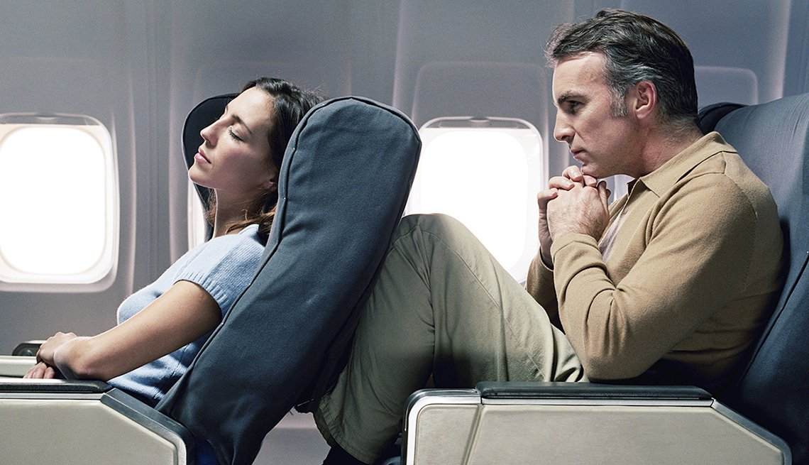 woman reclining airplane seat into a man's legs