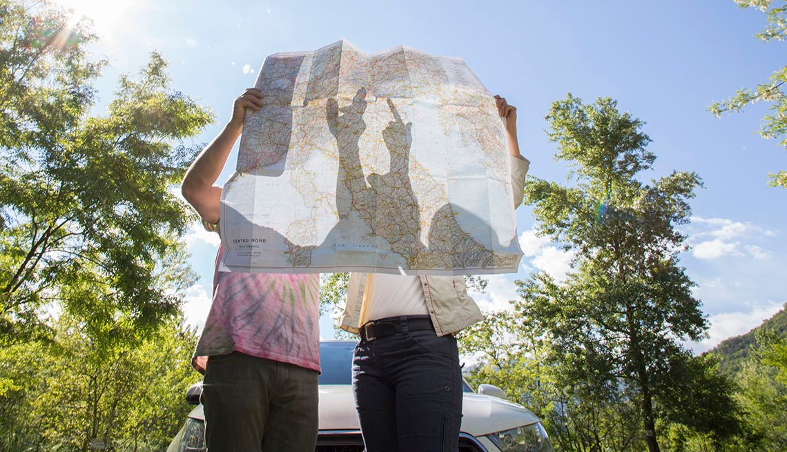 A Couple Looks At The Map With Their Car In The Background, Blue Sky, Outdoors, AARP Home And Family, Road Trip Guide