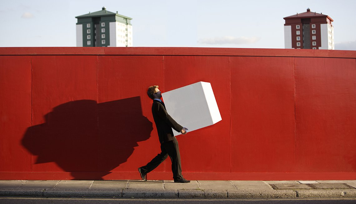 Man In Suit Holding Large White Box Walking Down Sidewalk With Red Wall Behind Him, AARP Work, Career Change, How To Negotiate A Killer Severance Package