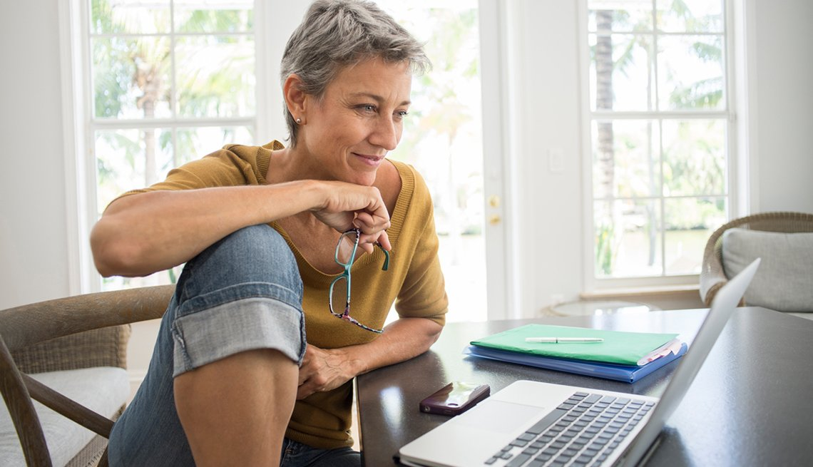 A middle aged caucasian woman looks at her laptop top in her home.