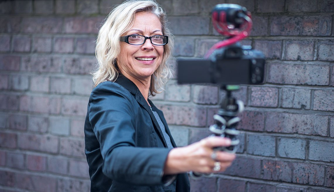 Professionally dressed, smiling woman taking video of herself
