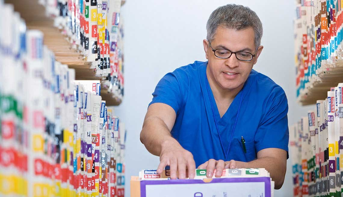 Man Putting Medical Records in Cart