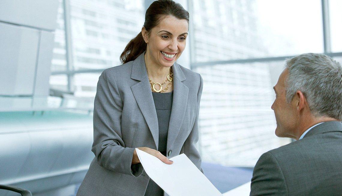 Mujer de pie entregándole un documento a un hombre sentado - Qué hacer cuando tu cargo laboral está desactualizado