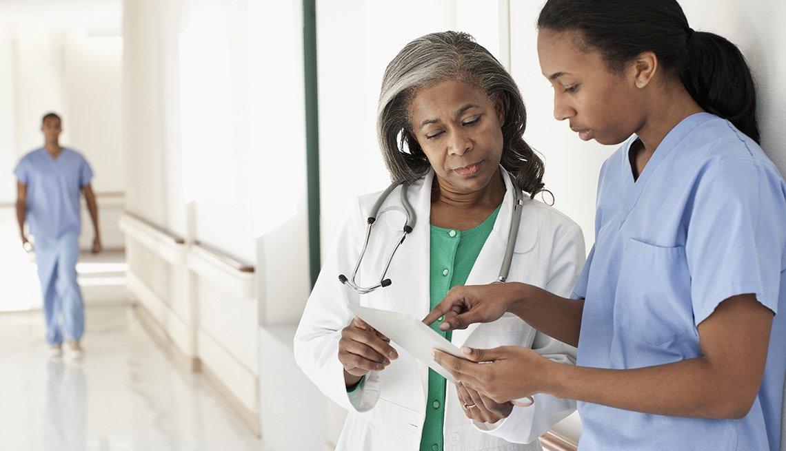 482142605Doctor and nurse talking in hospital corridor