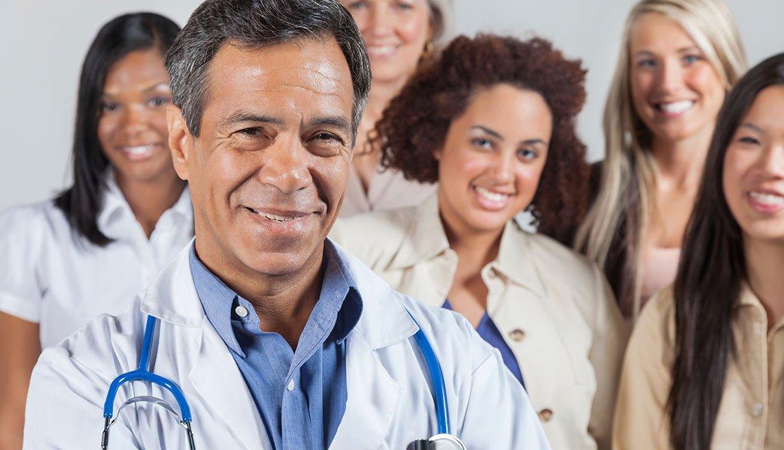 Médico hispano delante de un grupo de personas, cremiento de empleos