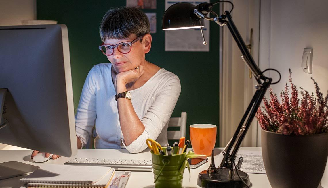 Mujer mayor frente a su computadora en casa