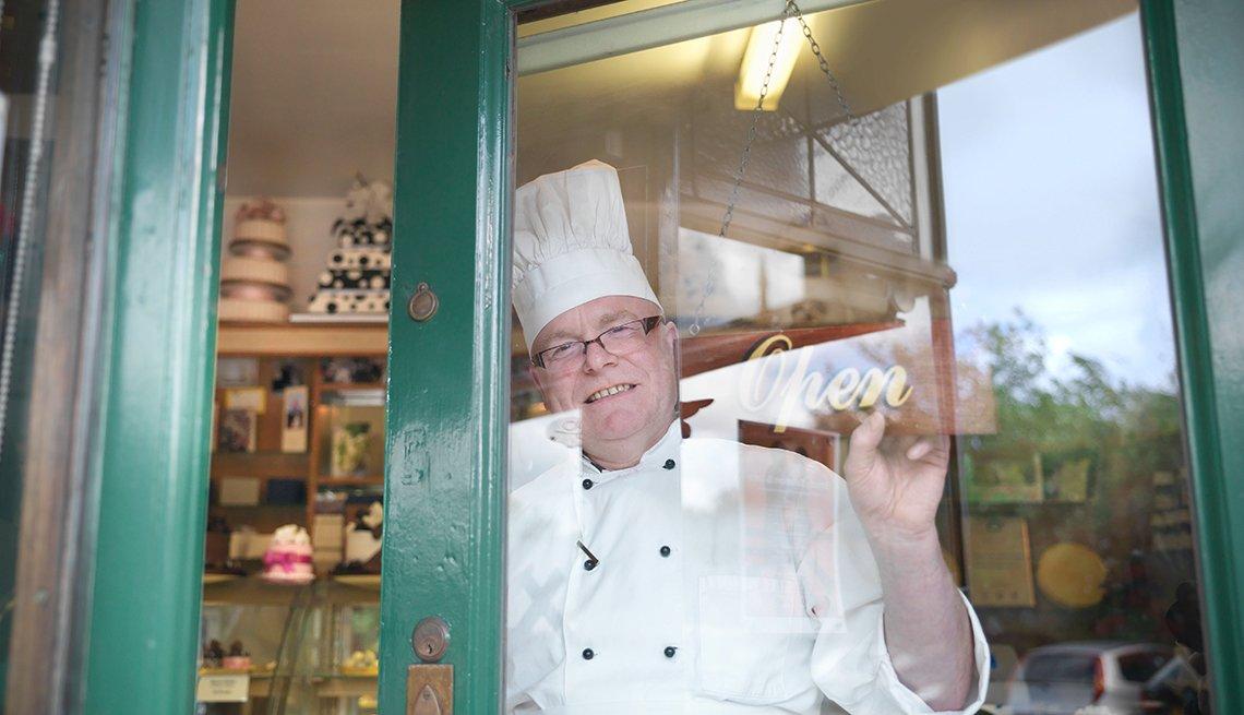 Hombre con traje de chef detrás de la puerta de una pastelería