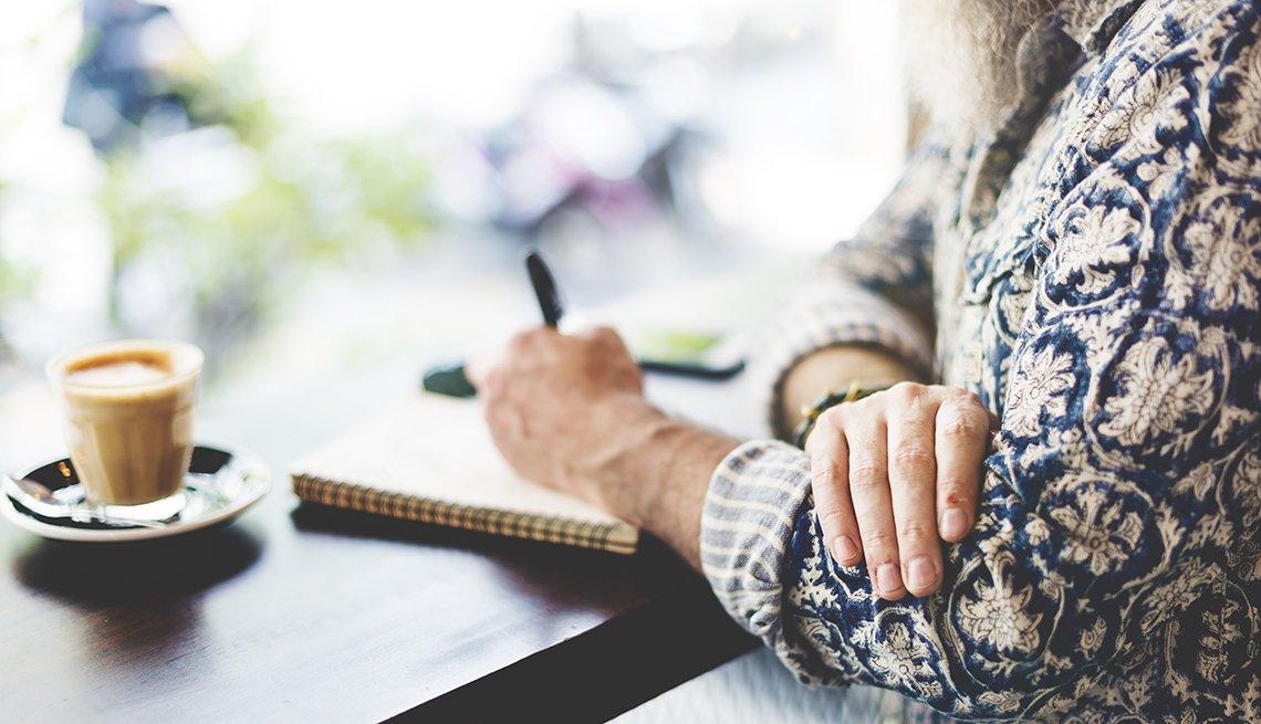 Manos de una mujer con un lapicero escribiendo en un cuaderno - Empleos con un salario anual superior a los 100 mil dólares