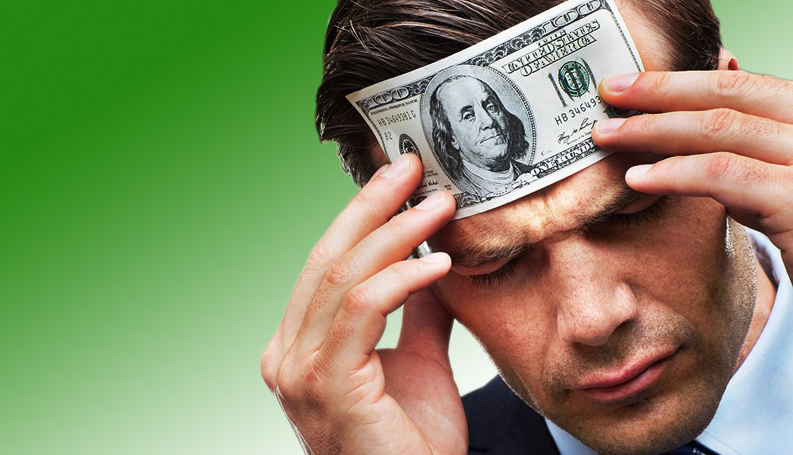 Man with a $100 bill pressed to forehead
