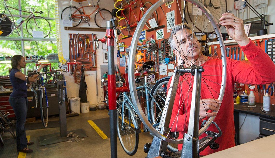 mature man repairing a bike in a shop