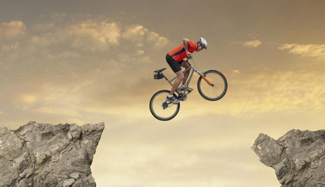 Man on Bicycle Jumping Between Rocks