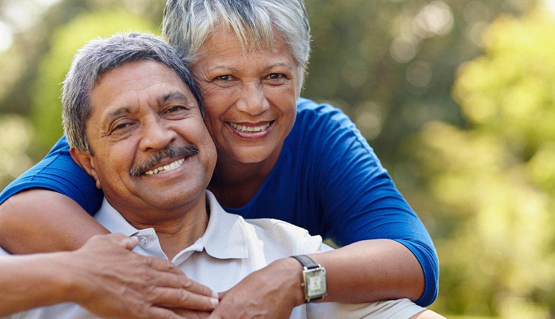 Hombre y mujer abrazados mirando a la cámara - Seguro Social ayuda a los cónyuges