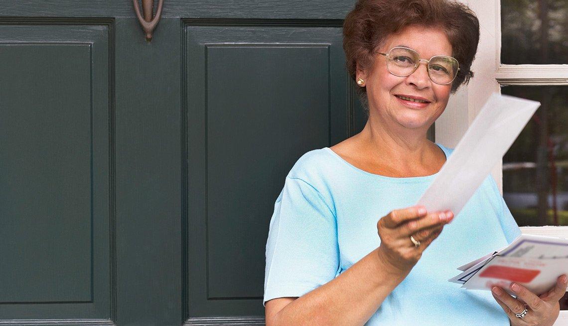 Mujer mayor con sobres de correspondencia en la mano - Seguro Social ayuda a los cónyuges