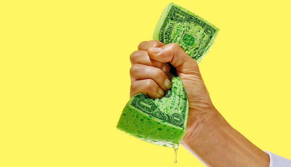 Mano cerrada sosteniendo una esponja verde con un billete de dólar grabado