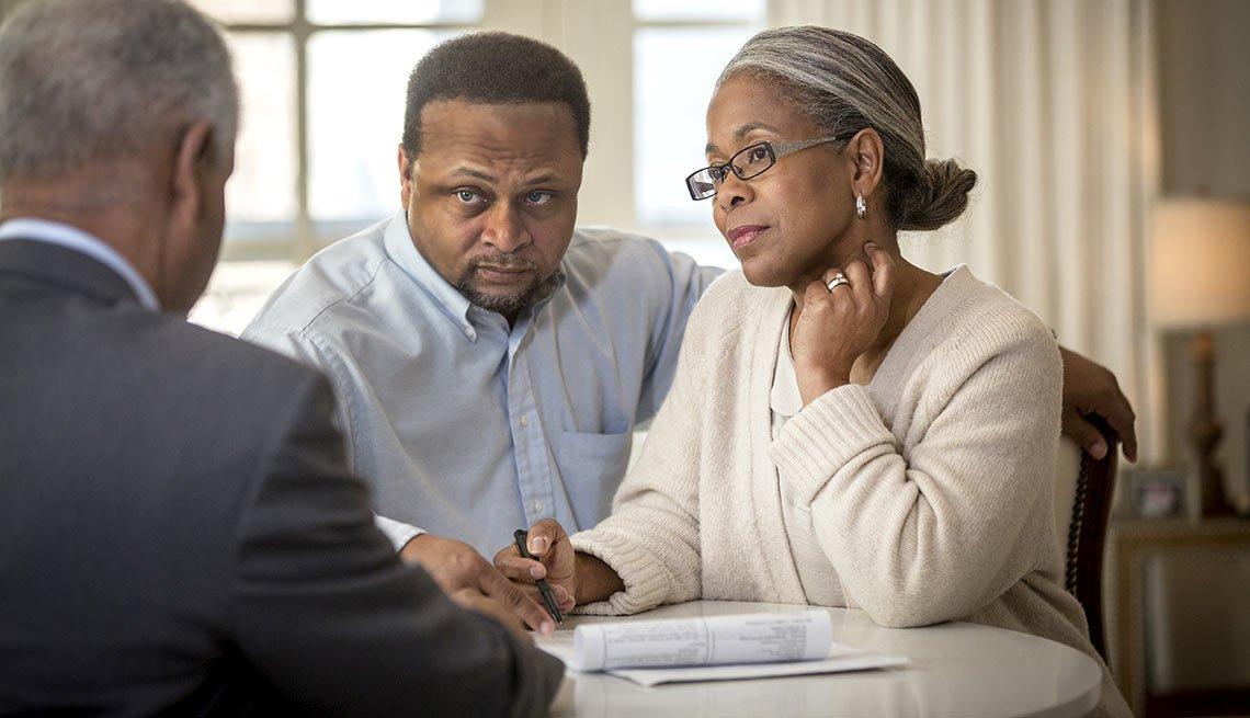 Pareja mayor frente a una mesa escuchando a un hombre en traje de corbata - Formas para realinear tu jubilación en pareja