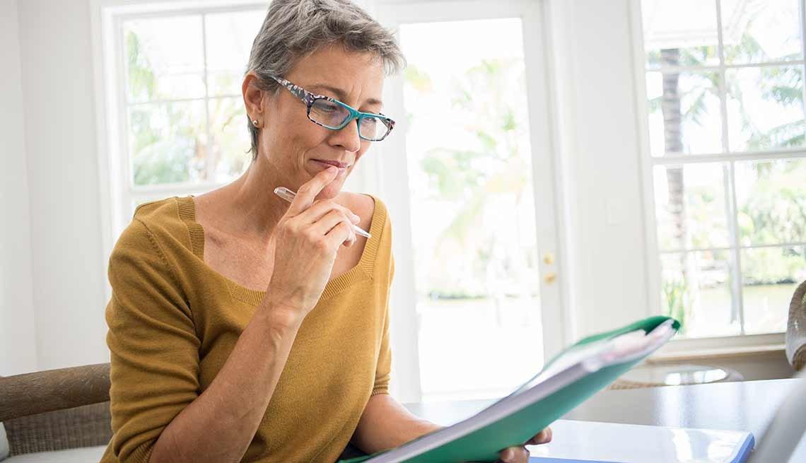 A woman calculates if she eligible for Social Security / Mujer haciendo cuentas en su casa