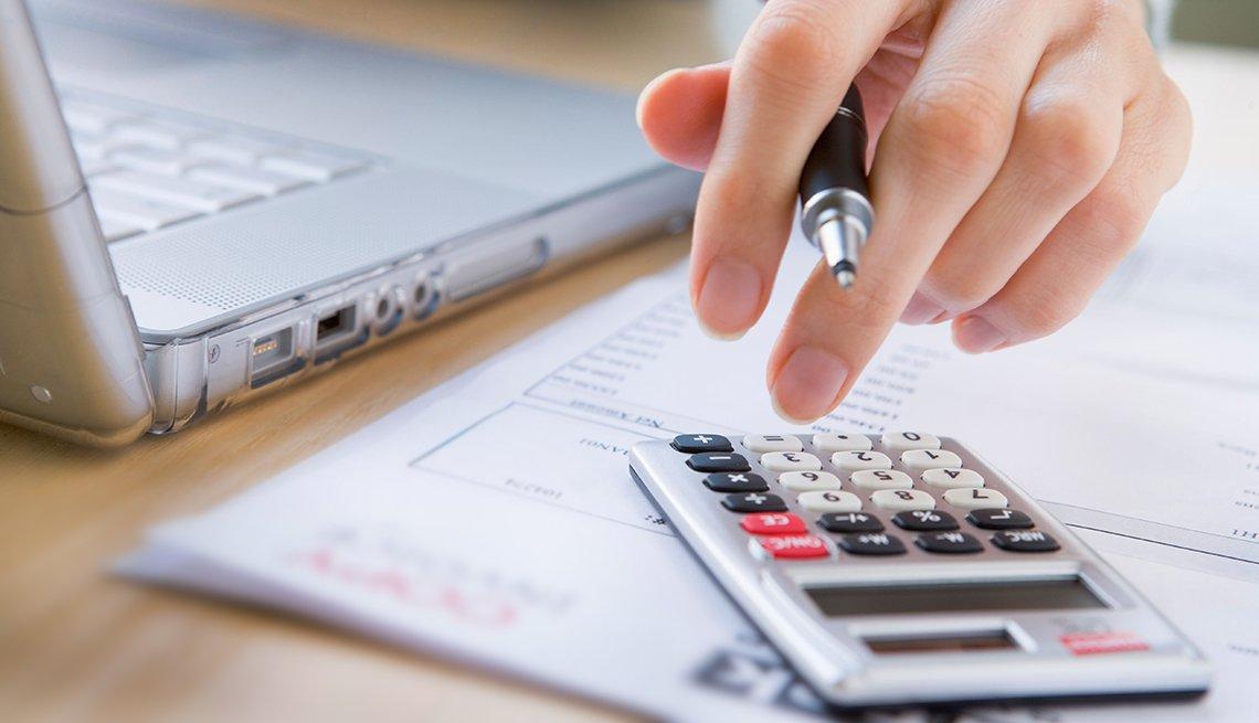 Mano tocando una calculadora con un lapicero en la mano