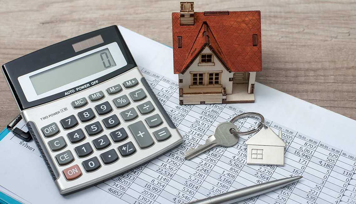 calculator and a toy house on top of a mortgage spreadsheet and a house key