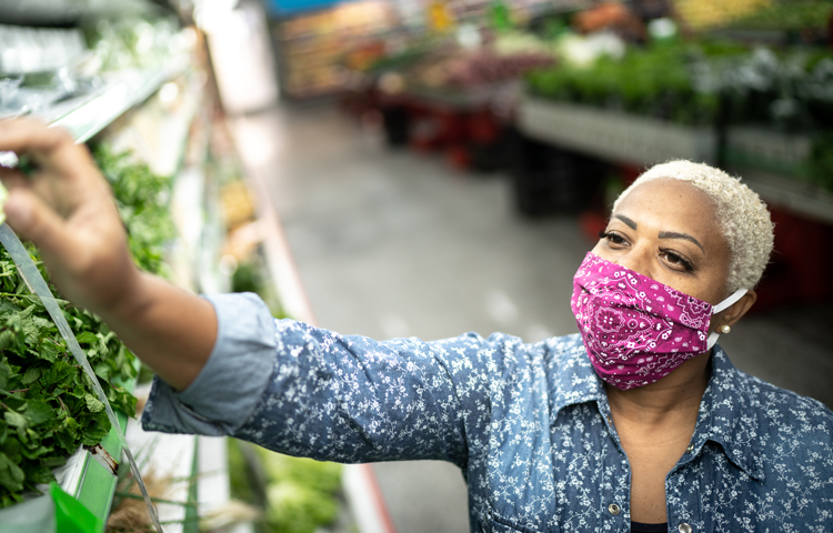 A woman wearing a face masks as she shops for produce