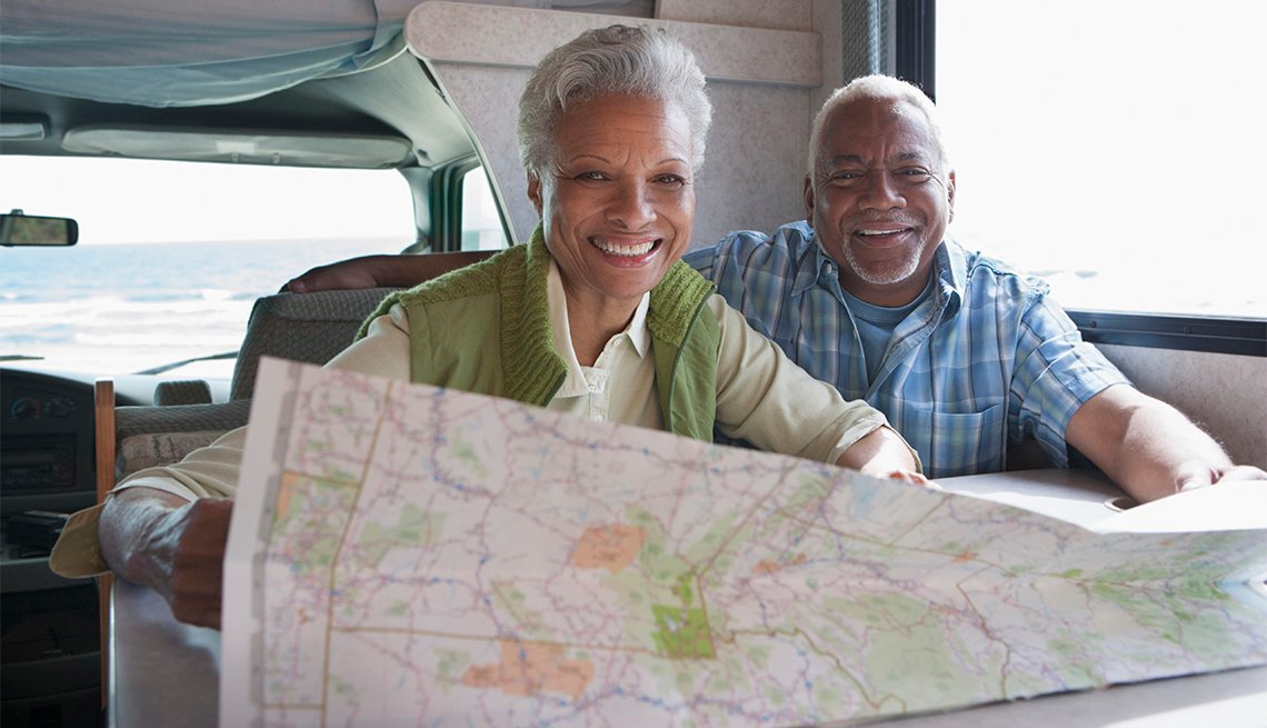 couple seated in camper looking at a map