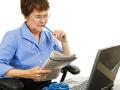 Mujer mayor sentada viendo el periódico, con lapicero en la boca y frente a una computadora portátil - Fraude de reclutadores de empleo en LinkedIN