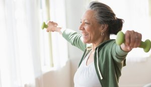 Older-Hispanic-woman-lifting-weights-in-living-room