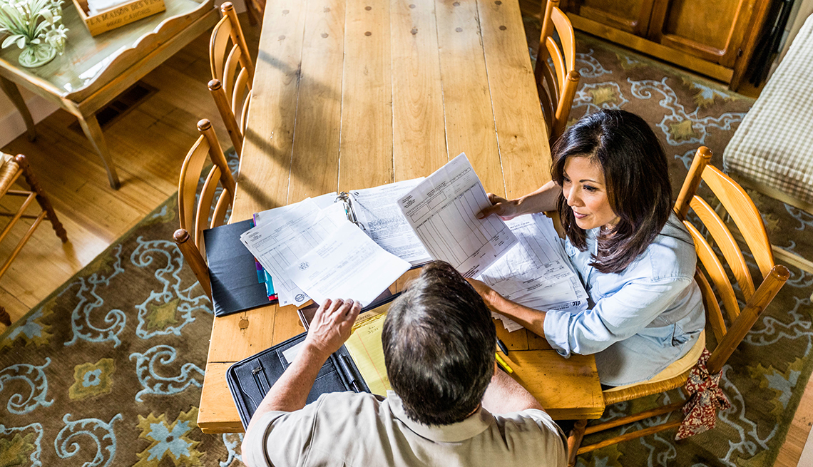 item 9 of Gallery image - Couple looking at paperwork at kitchen table