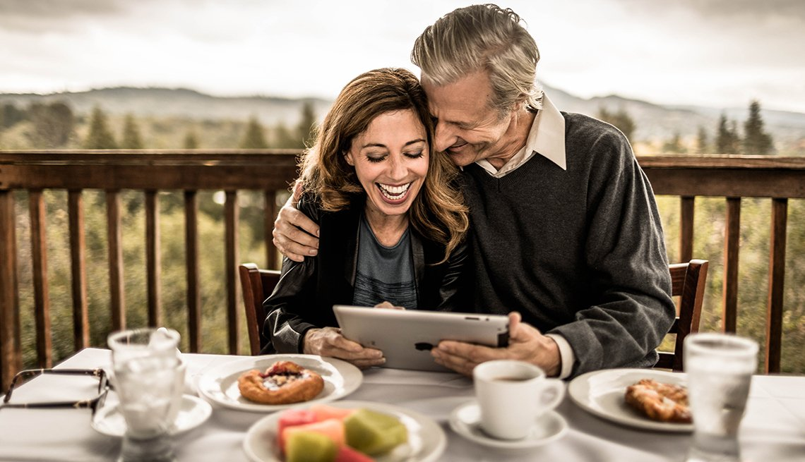 item 10 of Gallery image - Couple outside on a deck looking at a tablet and laughing