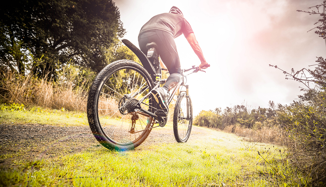 item 4 of Gallery image - Low angle rear view of man riding mountain bike on grassy trail