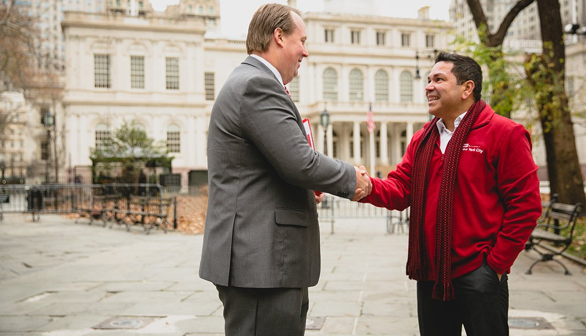 Men shake hands in a park. Caucasian Man in suit and tie. Hispanic man in red A A R P New York City jersey