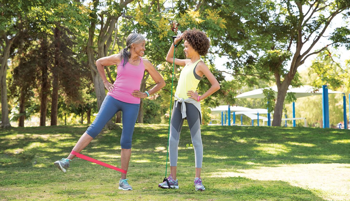 Senior African-American woman stretching legs with younger african-american woman in tree-shaded park