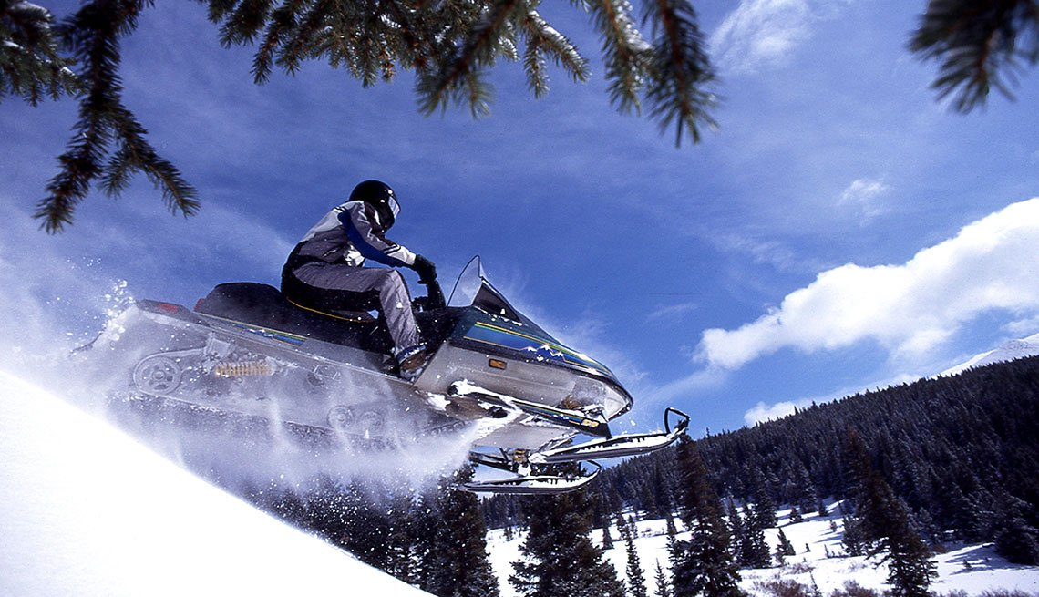 Man Driving Snowmobile Flying Through the Air, Breckenridge, Colorado, AARP Member Benefits Insurance