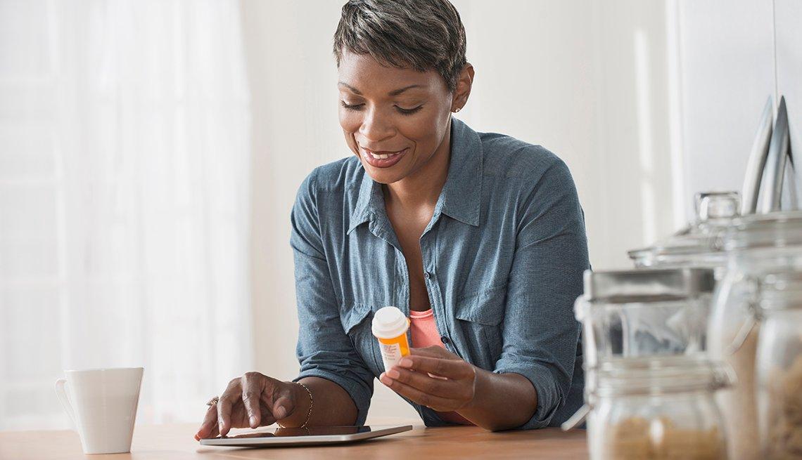 Una afroamericana sostiene en la mano izquierda un frasco de medicina mientras mira su tableta